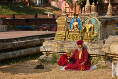 Old man in dress of monk sitting and praying Royalty Free Stock Photos