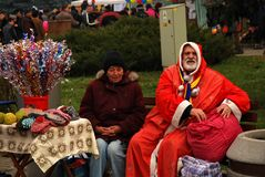 Santa and his wife inviting to gift. An old man dressed as santa, and his wife, inviting to see their homemade gifts and winter socks Royalty Free Stock Photos