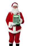 Old man dressed as Santa showing a calculator. Old man dressed as Santa showing a large green calculator to the camera Stock Image