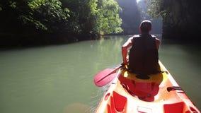 Old man drifts on kayak down river along sunlit canyon stock video