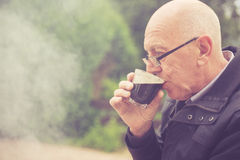 Old man drinkin in garden. An old man is drinking in a garden with smoke from a barbecue in the background stock photos