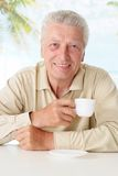 Old man drinking coffee at table Stock Photo