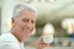 old man drinking coffee at table Stock Photography