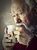 Old man drinking Stock Photography