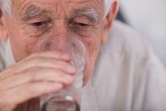 Old man drinking water Stock Photos