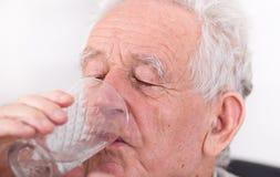 Old man drinking water Stock Image