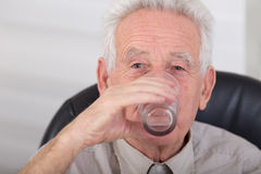 Old man drinking water. Senior man drinking water and looking at camera Royalty Free Stock Photography