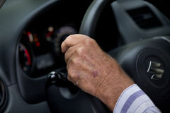 Old man driving car. Close up of old man`s hand on steering wheel in car Royalty Free Stock Image
