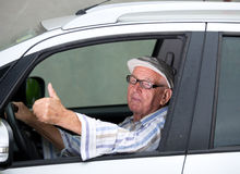 Old man driving car. Smiling senior man driving car and showing ok sign Royalty Free Stock Photos