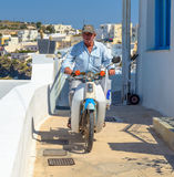 Old man driving by motorcycle at Santorini Island Stock Photo