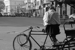 Poor old man wait for customer on his tri cycle for livelihood. An Old man earns his living by pulling passengers on back seat of his manually operated rickshaw royalty free stock photos
