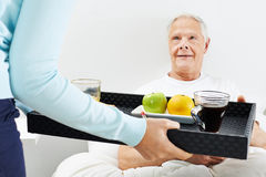 Old man eating breakfast in bed Stock Image
