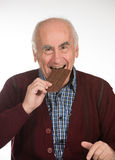 Old man eating chocolate royalty free stock photos
