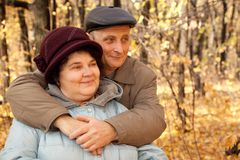 Old man embrace old woman in autumnal forest. Day Stock Image