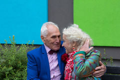 Old man embracing old woman`s shoulders outdoors.  Couple smilin Stock Photos