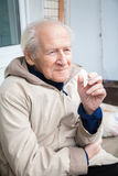 Old man enjoying a cigarette Stock Images