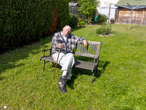 Old man enjoys sitting on a bench Stock Image
