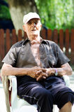 Old man enjoys sitting Stock Photography