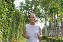 Old man exercise by jogging at the park, health concept, senior man smile and run outdoor Stock Photography