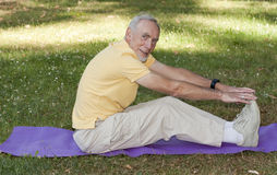 Old man exercising on mat in park Royalty Free Stock Photo