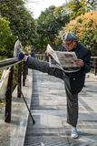 Old man exercising stretching splits gucheng park shanghai china. Shanghai, China - April 7, 2013: one old man exercising stretching splits and reading newspaper Stock Images