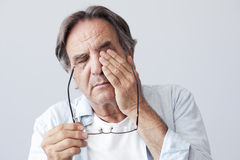 Old man with eye fatigue. On grey background royalty free stock photo