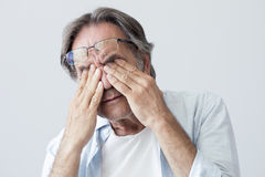Old man with eye fatigue. On grey background Stock Photos
