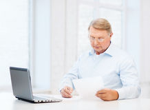 Old man in eyeglasses filling a form at home Royalty Free Stock Photos