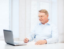 Old man in eyeglasses filling a form at home. Business, tax, office, school and education concept - old man in eyeglasses filling a form at home Stock Image