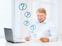 Old man in eyeglasses filling a form at home Royalty Free Stock Photography