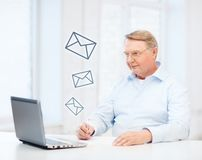 Old man in eyeglasses filling a form at home Royalty Free Stock Image