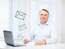 Old man in eyeglasses filling a form at home Stock Image