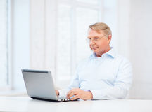 Old man in eyeglasses working with laptop at home Stock Photos