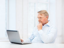 Old man in eyeglasses working with laptop at home Royalty Free Stock Photos
