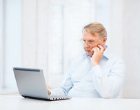Old man in eyeglasses working with laptop at home Stock Photography
