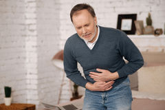 Old man feeling big discomfort in stomach. Very hurtful. Poor senior man standing and holding his hands on stomach area because of strong pain Stock Photo