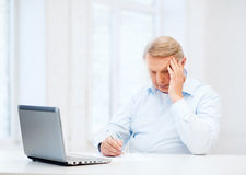 Old man filling a form at home Stock Image