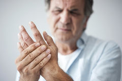 Old man with finger pain. On grey background stock photo