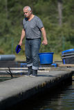 Old man fish farm worker carries bucket Stock Image