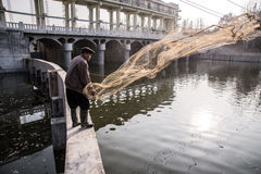 Old man fishing on the river. An old man casts a net into the river, Huai River Basin, Henan, China. (circa December 2013 Royalty Free Stock Image