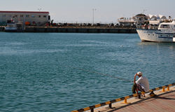 Old man fishing in the sea port Royalty Free Stock Image