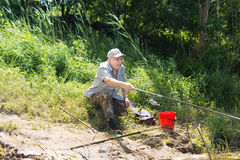 Old man fishing sitting on the grass Stock Image