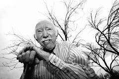 Old man in front of bare trees. Crazy old man leaning on cane in front of trees Stock Photo