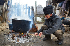 Old man fueling fire to boiling pots outdoor Royalty Free Stock Photography