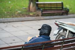 Old man with full leather hat reading book in park.  Stock Photo