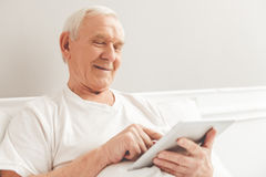 Old man with gadget Royalty Free Stock Photography