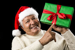 Old Man With Gentle Smile Pointing At Green Gift. Venerable male senior with a broad smile is pointing at a green gift raised high with his left hand. The Royalty Free Stock Photography