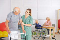 Old man with geratric nurse in nursing home. Old men standing with geratric nurse in nursing home with senior people royalty free stock photos
