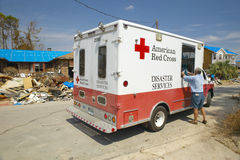 Old man getting bag of ice from Red Cross vehicle Stock Photo