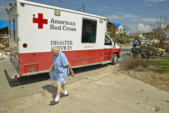 Old man getting bag of ice from Red Cross vehicle Stock Image